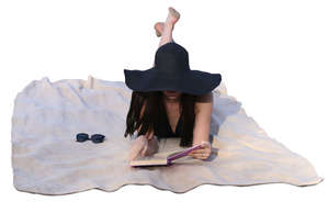 woman with a black hat reading a book on the beach