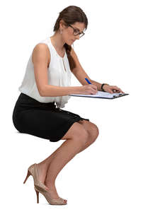 businesswoman sitting at a desk and writing