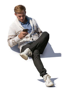 man sitting and checking his phone