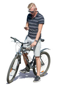 man with a bicycle standing and checking his phone