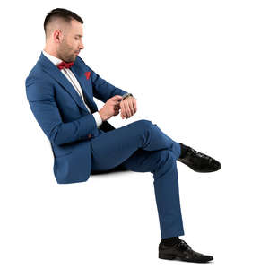 man in a blue suit sitting and checking his watch