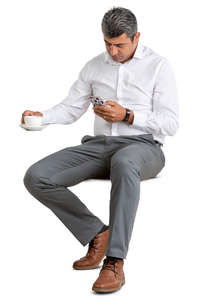 man in a suit sitting in a cafe and drinking coffee