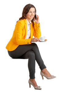 woman sitting in a cafe and talking on a phone