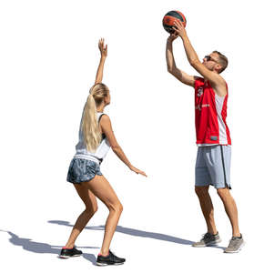 man and woman playing basketball outside