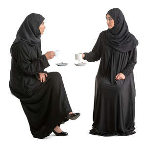 two arab women in abayas sitting in a cafe