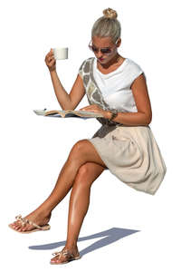 woman drinking coffee and reading a magazine