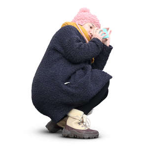 asian woman in winter coat squatting and taking a picture