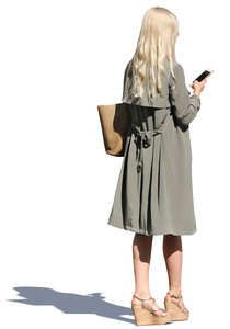 woman in a light trenchcoat standing and texting