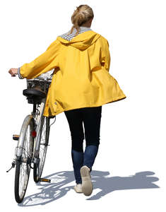 woman with a yellow raincoat pushing a bike