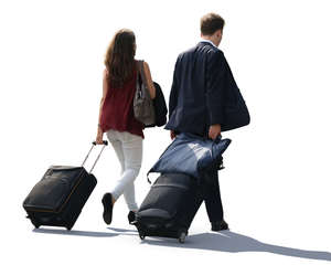backlit man and woman pulling big suitcases