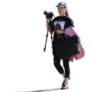 backlit asian woman walking and carrying a camera and tripod