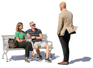 two people sitting talking with a standing man