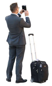 businessman with a suitcase standing and taking a picture