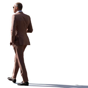 backlit man in a brown suit walking