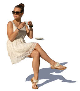 woman in a white summer dress sitting in a cafe