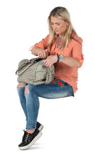 woman sitting and opening her handbag