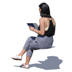 asian woman sitting and looking at tablet