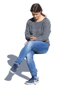 woman sitting and looking at her phone