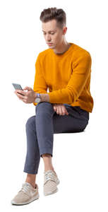 young man sitting and looking at his phone
