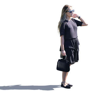 sidelit woman in a black summerdress standing