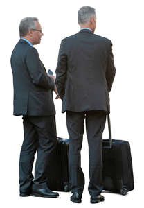two businessmen with suitcases standing