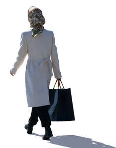 backlit woman with a headscarf walking