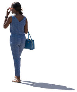 backlit woman in a blue jumpsuit standing