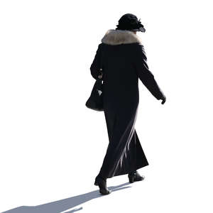 backlit woman in a winter coat walking