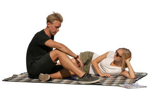 man and woman sitting on a picnic blanket and talking
