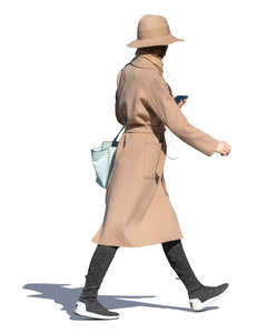 woman in a brown overcoat and hat walking