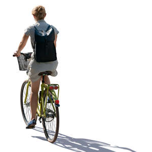 backlit woman riding a bicycle