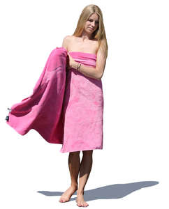 woman standing and wrapping a pink towel around herself