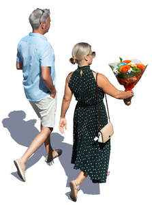 man and woman walking and carrying flowers seen from above