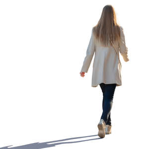 backlit woman in a light overcoat walking
