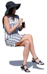 woman in a summery outfit sitting and holding a drink