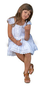little girl in a white dress sitting