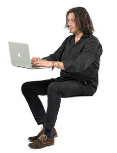 man sitting at a desk and working with laptop