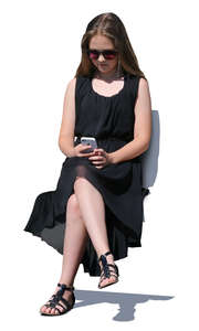 girl in a black dress sitting and looking at her phone