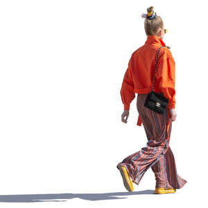backlit woman in a colorful outfit walking