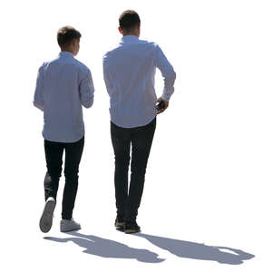 two backlit teenage boys walking