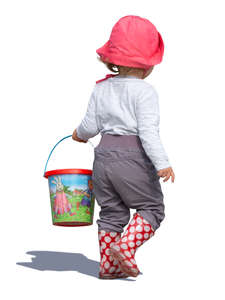 little girl with a toy bucket walking