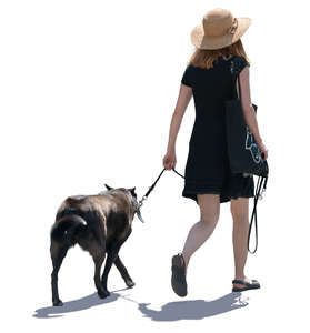 backlit woman walking a dog
