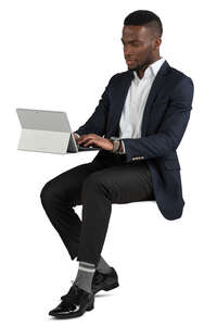 black man sitting and working with laptop