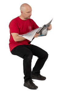 man in a red shirt sitting and reading a newspaper