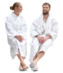 man and woman in bathrobes sitting in a spa and talking