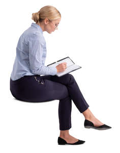 woman in an office sitting and writing