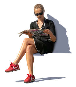 woman sitting on a bench and reading a magazine