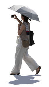 backlit woman with parasol walking