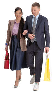 man and woman with shopping bags walking arm in arm