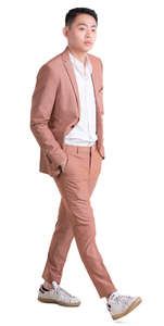 asian man in a pink suit walking